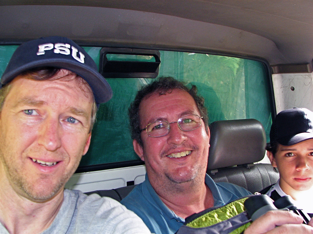 Jim Marden and Eduardo Carrillo riding in the back seat of a very bumpy pickup truck on a muddy mountain road, Costa Rica.