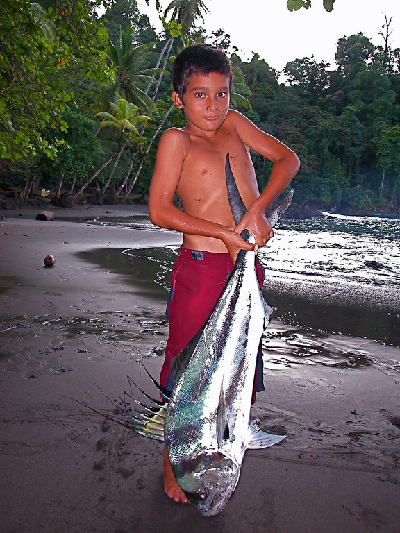 Cristian, age 9, on the beach he grew up on, with a rooster fish (Nematistius pectoralis) larger than he can lift.  Caught on a handline off of the shore at Campanario, Osa Peninsula, Costa Rica.
