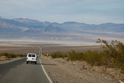 SJSU van entering Death Valley.  Stovepipe Wells is peeping over the rise in the mid-distance.