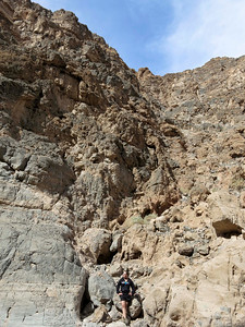 Class member posing at the base of a wall in Titus Canyon.
