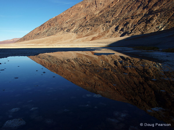 The hills near Badwater, Death Valley National Park are reflected in the pool of salty water.  The lowest place in Death Valley and all of North America, is near this pool and is 282 feet below sea level.