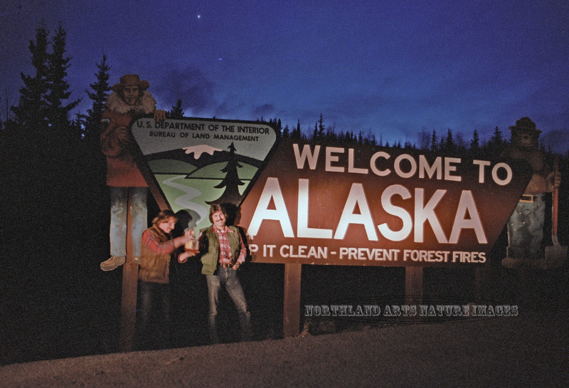AK-1980.4#50b. Tom and Joe Romero at the Alaska/Yukon border. Celebrating our getting back home to Alaska from Denver Colorado with some of Des Muligan's houch.