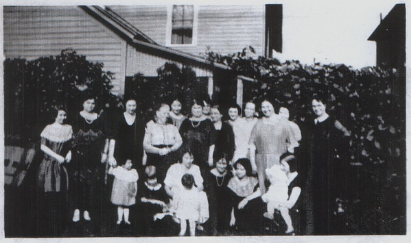 Family gathering. My mother is the little girl towards the front, dressed in white, whith her head down.