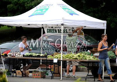 8/3/2011 Mike Orazzi | Staff Whit Betts hangs the sign at the Green Acres Farm stand during the Bristol Farmers' Market held at the Bristol Commons shopping center during the weekly Wednesday market.  *** for a Diane Sunday story ***