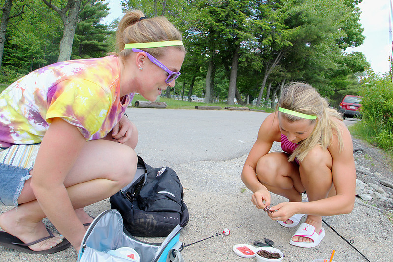 Lindsey Noseworthy, 22, of Westminster helps her friend Chelsea Richard, 23, of Gardner put some new bait on her hook as they fished at Round Meadow Pond in Wesminster on Tuesday afternnoon. It was Richard's first time fishing. SENTINEL & ENTERPRISE/JOHN LOVE