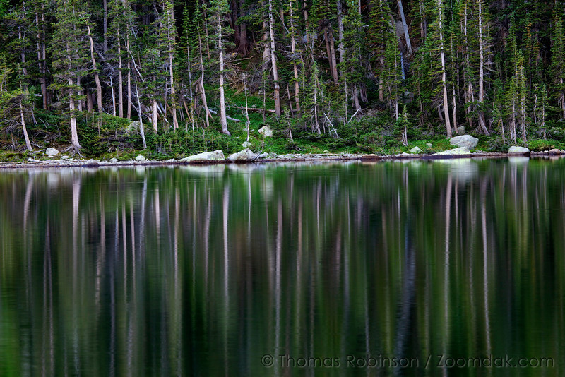 A evening waters of Thunder Lake make a beautiful reflection of the forest.