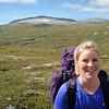 Silje med Blåhøa i bakgrunnen. På andre siden av den bakerste høyden der gikk vi første dagen, så nå begynner vi å se for oss enden på turen.