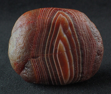 "2.5-oz Lake Superior Agate; 4.5cm x 3.5cm x 3cm (about the size of a chestnut).   ""Water polished"" - the smooth appearance is due to water running over the surface; the stone was probably in a creek bed. A ""healed"" fracture runs across the face. Has a beautiful banding design that looks like a lit flame."