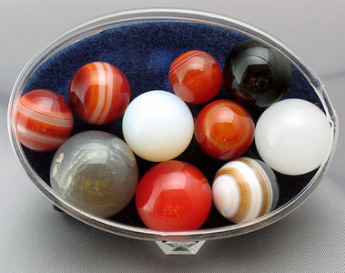 A collection of agate marbles; from 1.2cm to 2cm in size.   It looks to be a mixture of Brazilian agates and various solid color quartz spheres. I purchased these years ago at a garage sale for less than $2.50 for the group.
