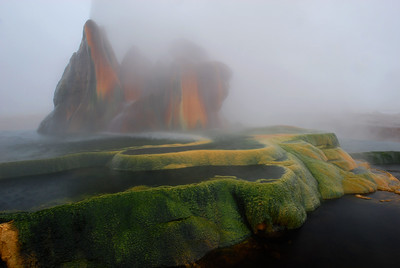 Colorful mineral pools deposited by the hotsprings geyser water, supersaturated with dissolved minerals that precipitate out as the water cools; surrounded by clouds of steam.