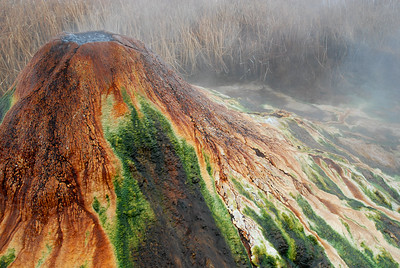 Geothermal geyser boiling over, depositing minerals into a massive mound with colorful thermophilic bacteria growing along the rivulets of outflow.