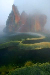© Joseph Dougherty. All rights reserved.   Colorful mineral pools deposited by the hotsprings geyser water, supersaturated with dissolved minerals that precipitate out as the water cools; surrounded by clouds of steam.
