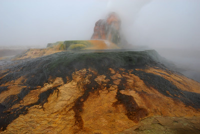 Colorful hotsprings geyser and mineral pools surrounded by clouds of steam.