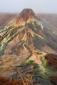 © Joseph Dougherty. All rights reserved.   Geothermal geyser boiling over, depositing minerals into a massive mound with colorful thermophilic bacteria growing along the rivulets of outflow. Different colors of bacteria live at different temperatures along the geyser face.