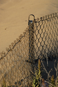 A shifting wind-blown sand dune threatens to encroach on developed property and engulf a nearby fence.