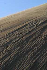 A wind-swept sand dune with ripples like waves across its surface.