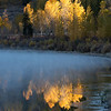 Early morning fall color reflections in Two Ocean Lake after a cold night, with mist and the shoreline iced over.  Grand Teton National Park, Wyoming, USA