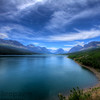A blue mountain lake with thin white clouds shoot in High Dynamic Range.