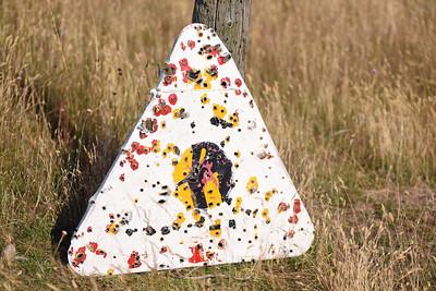 Sönderskjuten skylt på Ravlundafältet (skjutfält)