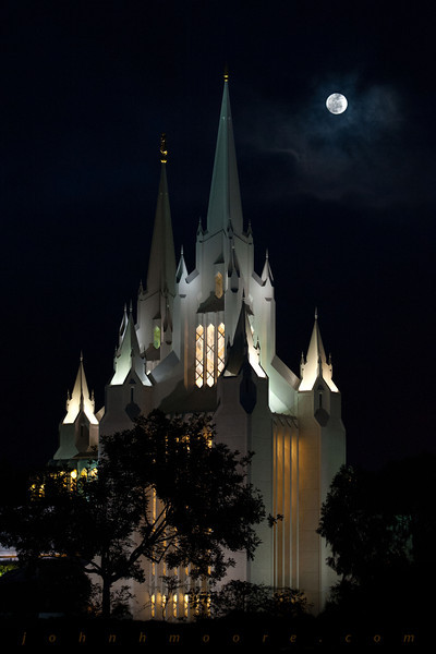 The full moon finds a hole in the heavy cloud cover behind the San Diego Mormon Temple