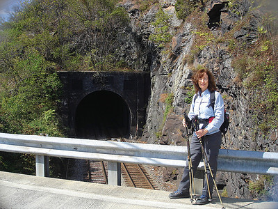 Donna standing on Sandy Hook Road above railroad track at the east end of the tunnel.  We came down from the cliffs on Maryland Heights by way of herd path.