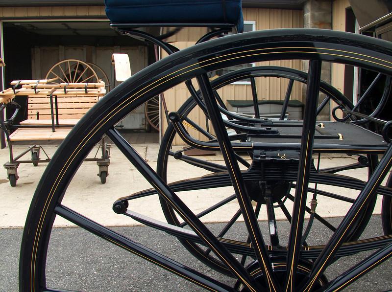 Jason Stolzhus' carriage shop, amazing craftmanship. Amish boy sands wheels in background
