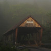 Bump covered Bridge glows in the early morning fog.  Campton, NH.