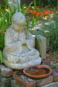 © Joseph Dougherty.  All rights reserved.   Buddhist monk statuette with flowers in the garden.