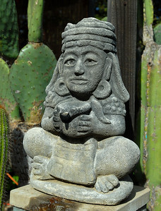 © Joseph Dougherty. All rights reserved.  Aztec statuette with cactus in the garden.