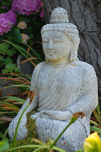 © Joseph Dougherty.  All rights reserved.   Buddha statuette with flowers in the garden.