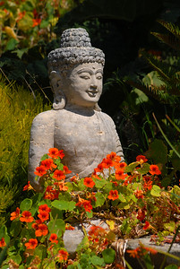 © Joseph Dougherty. All rights reserved.   Buddha statuette with orange flowers.