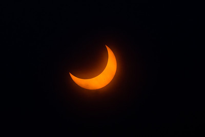 Crescent sun of annular eclipse. The dark spot is a sunspot and the shadows are from clouds.