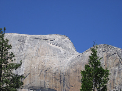Half Dome from the rounded southern back side. Light line ascending from right to left is the area of the cable stairway, lighter in color as hikers over the years have worn through the patina of the dome; dots along it are people hiking up or down. View at maximum resolution and the dots resolve to human figures.