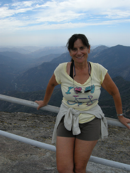 Michèle atop Moro Rock, with view to west. The Central Valley is beyond the far foothills. A forest far to the north had made the visibility a bit hazy.