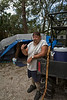 Volunteer Jeff Lachar at his camp site with one of his hand-carved walking sticks.