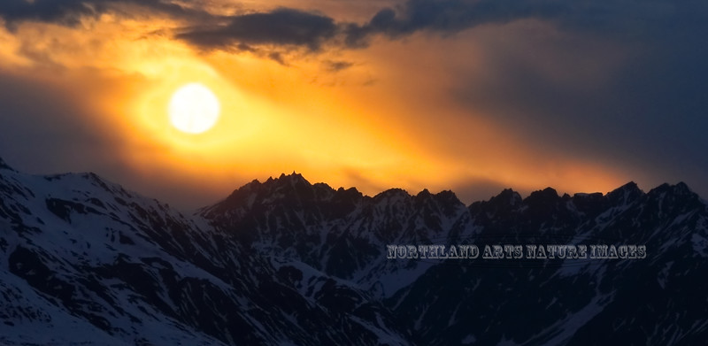 A storm in the central Alaska Range surrounds the midnight sun. #521.009.