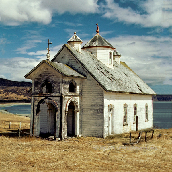1984.5#42. The Holy Resurrection Church in Belkofski was built by the Russian Orthodox Mission. Earliest evidence of this building go back to 1879 when a church account stated their were 650 Orthodox souls living in Belkofski. The oldest printed evidence from a Sitka newspaper recognize this building in 1887. Among other unique features this is one of very few churches of the era that did not have an Onion Dome. Instead it had three pyramidal cupolas. I was fortunate to get to visit this before it collapsed and burned. I have photos of the inside that I will add to this site in the future. The church bell and many items from inside the church were saved by the people of King Cove and now reside in St. Herman Church in King Cove. What isn't in King Cove was taken to other Churches. Belkovski Village, Alaska Peninsula, Alaska.