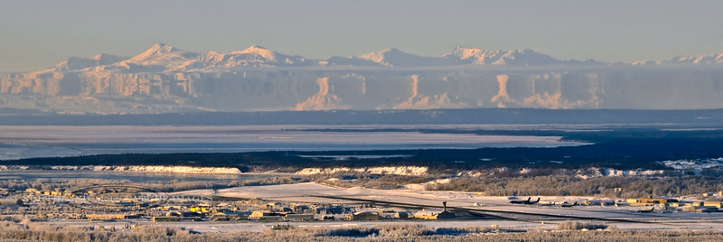 "The west end of JBER runway appears as any normal clear mid winter mourning, but the ""Fata Morgana"" transforms the Alaska Range across Cook Inlet into a surreal mirage. View from Anchorage, Alaska. 17.025."