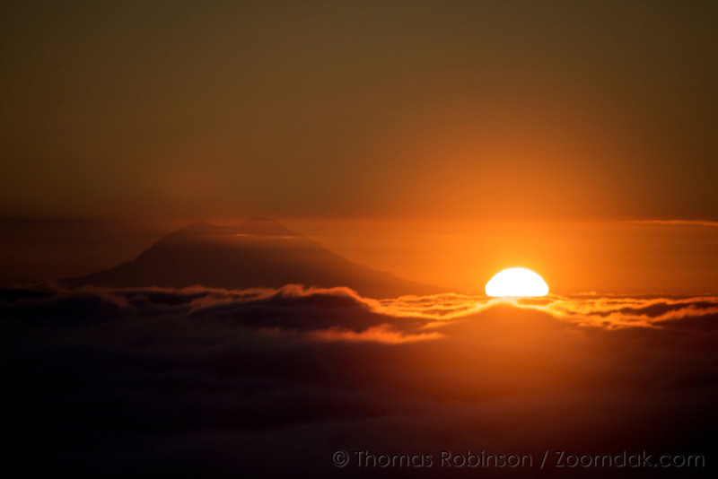 The sun rises over the clouds on the edge of Mt. Rainier.