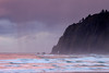 The Neahkanie Arch peeks out as rain clouds gather above the Neahkanie Cliffs at sunset in Manzanita, Oregon.