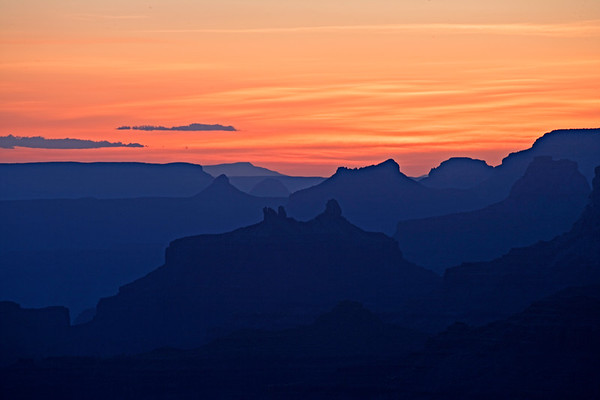 Sunset on the South Rim of the Grand Canyon with rock formations in silhouette.