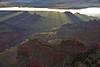 God rays streak under clouds and reveal the beauty of the Grand Canyon