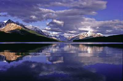 Mountains and clouds reflect in Lake Maligne in Jasper National Park, Alberta, Canada.
