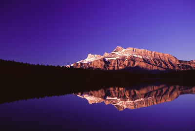 Rising sun casts a warm glow on Mount Rundle from Two Jack Lake near Banff, Alberta, Canada.