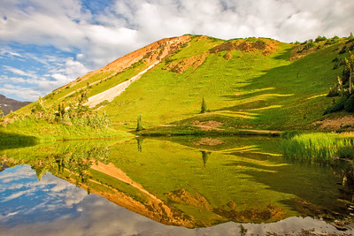 Fresh spring colors reflect streaking clouds in a small tarn near Paradise Divide between Aspen and Crested Butte, Colorado.