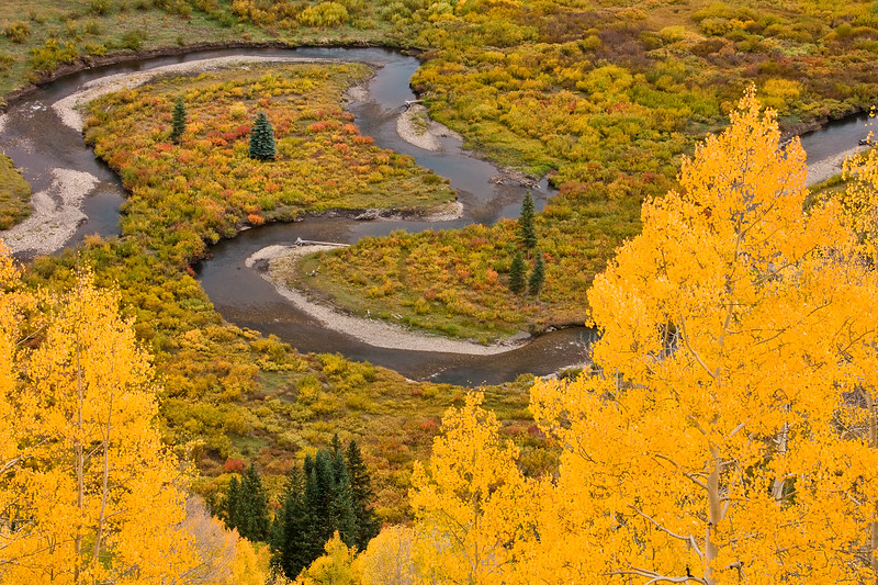 Copper Creek near Crested Butte winds through a valley flanked by autumn colors.  Viewed from Gothic Road outside Crested Butte, Colorado.