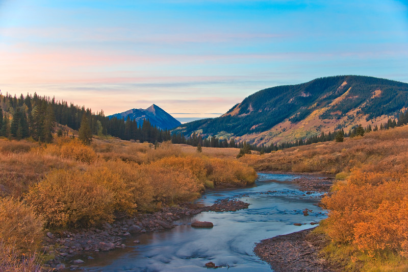 Autum sunrise touches Mount Crested Butte and golden willows line the East River west of the town of Gothic.
