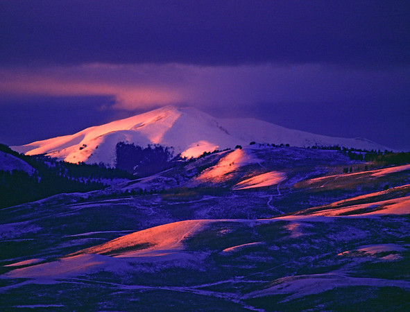 Pink delicate winter sunset light dances across a valley near Grandby, Colorado.