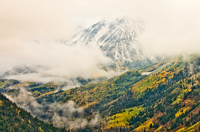 From McClure Pass, early snow and clearing clouds float above the Crystal River between Redstone and Paonia, Colorado.