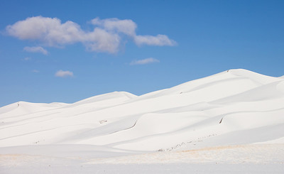A clearing overnight storm leaves clouds drifting above snow covered dunes in Great Sand Dunes National Park and Preserve.